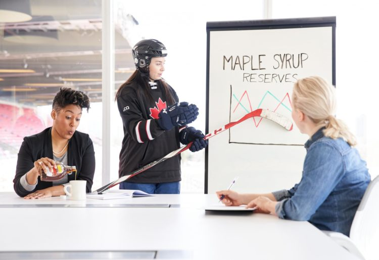 Colleague enjoys tasty glass of maple syrup during presentation by hockey player - Photo by Canadian Internet Registration Authority (CIRA)